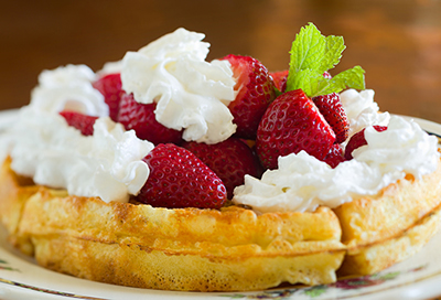Beautiful strawberry Belgian waffles with whipped cream